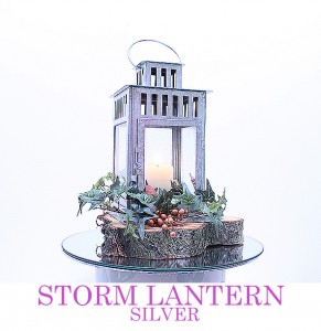 Silver Storm Lantern with pillar candle..decor to suit theme. Displayed on rustic wooden base
